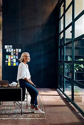 Portrait of casual mature businesswoman in loft office - p300m2144770 by Sofie Delauw