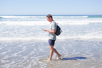 Full length side view of mature man using mobile phone while walking in sea at beach - p426m1451808 by Maskot