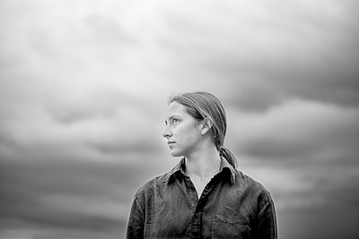 Portrait of young woman against dark clouds - p552m2289376 by Leander Hopf