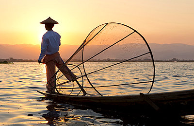 Intha 'leg rowing' fishermen at sunset on Inle Lake who row traditional wooden boats using their leg and fish using nets stretched over conical bamboo frames, Inle Lake - p871m819403 by Lee Frost