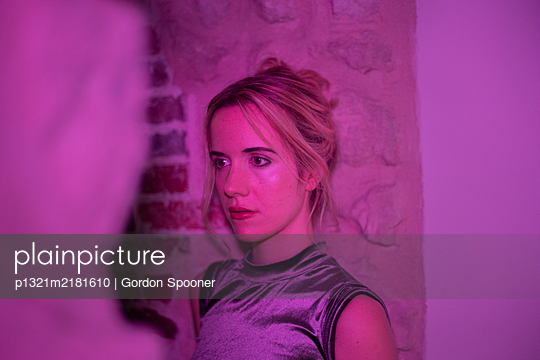 Young blonde woman in pink coloured light, portrait - p1321m2181610 by Gordon Spooner