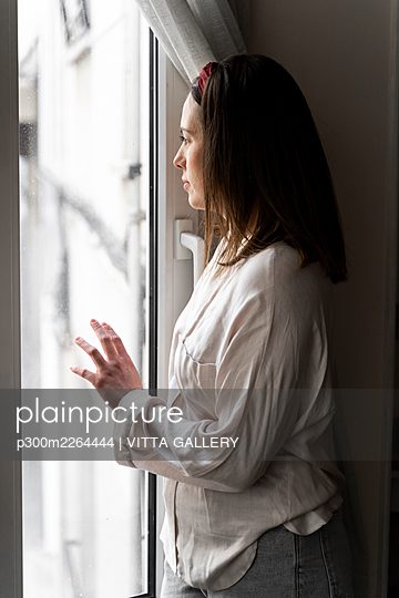 Thoughtful young woman looking though window while standing at home - p300m2264444 by VITTA GALLERY