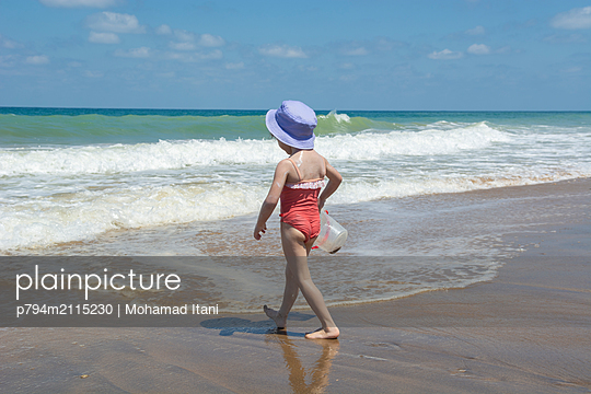 Little girl walking on the beach  - p794m2115230 by Mohamad Itani