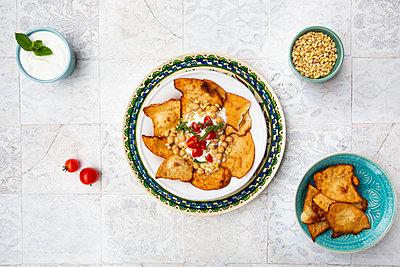 Fatteh (levantinisches Gericht, Frühstück oder Zwischenmalzeit, Mezze) geröstetes, in Stücke zerbrochenes Fladenbrot, Minz-Joghurt, Kichererbsen, Olivenöl, Tomate und Tahin - p300m2144035 von Larissa Veronesi