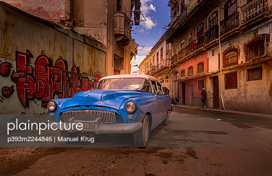 Blue classic car in front of housewall with graffiti, Cuba - p393m2244846 by Manuel Krug
