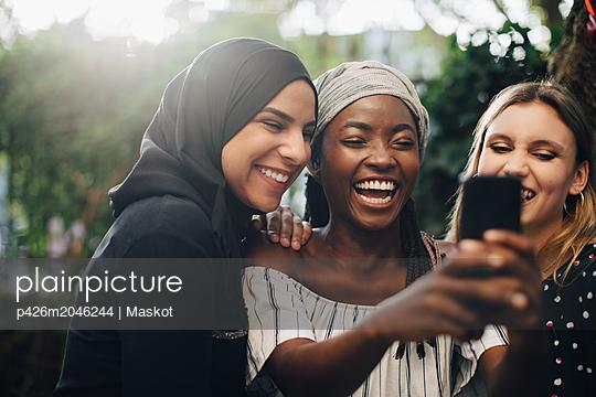 Smiling multi-ethnic female friends taking selfie through mobile phone in backyard - p426m2046244 by Maskot
