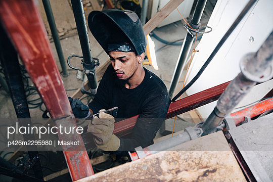 Young male welder wearing welding helmet while working at construction site - p426m2295980 by Maskot