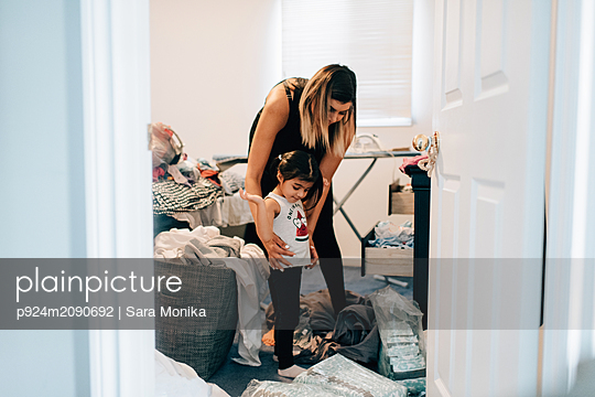 Girl getting dressed with mother in laundry room - p924m2090692 by Sara Monika