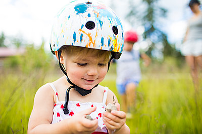 Young girl wearing helmet  enjoying time playing outside - p1166m2147327 by Cavan Images