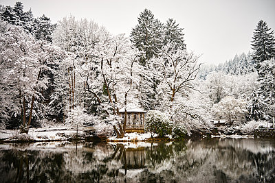Pavillion on the lake with snow-capped trees - p1312m2182153 by Axel Killian