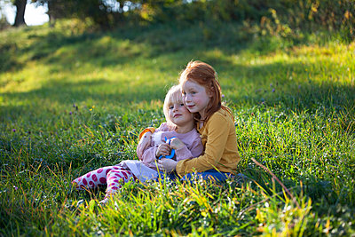 Two sisters cuddling in field - p300m2103564 by Anette Christina Götz