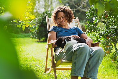 Smiling mid adult woman carrying cat while sitting in deck chair in garden - p300m2267369 by Steve Brookland