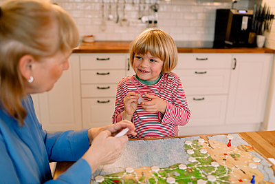 Happy grandson playing board game with grandmother at table - p426m2195049 by Maskot
