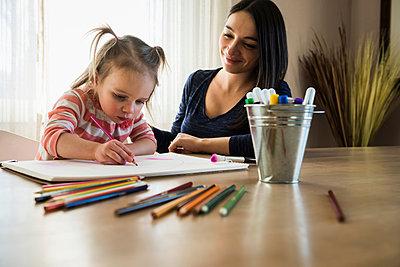 Female toddler at table with mother drawing in sketchbook - p429m1408115 by Mike Tittel