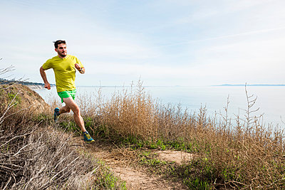 Runner jogging on cliff top, Santa Barbara, California, USA - p429m2075316 by JFCreatives