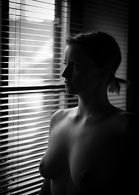Naked woman by the window - p552m2109632 by Leander Hopf