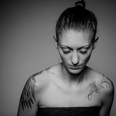 Tattooed woman, portrait - p552m2165701 by Leander Hopf