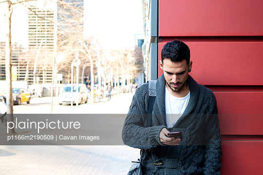 Front view of a bearded man using phone leaning on office building wall - p1166m2190509 by Cavan Images