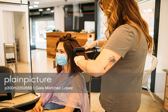 Female hairdresser with mask using straightening machine - p300m2202656 by Gala Martínez López