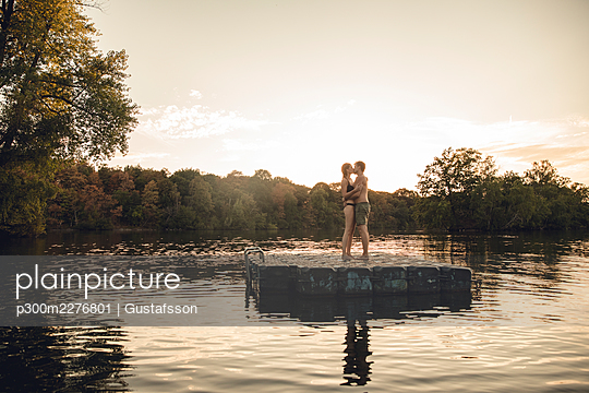 Young couple standing on bathing platform on a lake, embracing and kissing - p300m2276801 by Gustafsson