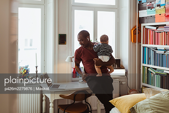 Businessman carrying male toddler while telecommuting through laptop at home - p426m2279876 by Maskot