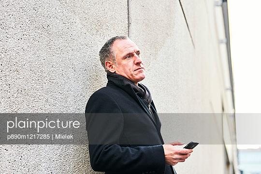 Mann lehnt an Wand und benutzt sein Handy - p890m1217285 von Mielek