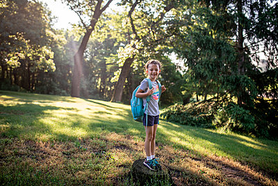 Portrait of girl with backpack standing on tree stump in forest - p1166m2009483 by Cavan Images