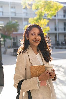 Portrait of smiling young woman with book and takeaway coffee in the city - p300m2166193 by VITTA GALLERY