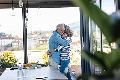 Senior couple embracing while standing by window at home - p300m2265849 by Emma Innocenti