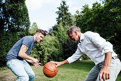 Father playing basketball with son in backyard during sunny day - p300m2276987 by Gustafsson