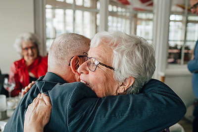 Senior man embracing woman while sitting in restaurant - p426m2149115 by Maskot
