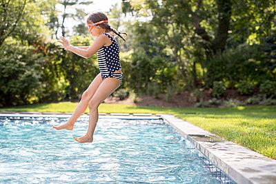 Girl jumping into outdoor swimming pool - p924m1404202 by Sasha Gulish