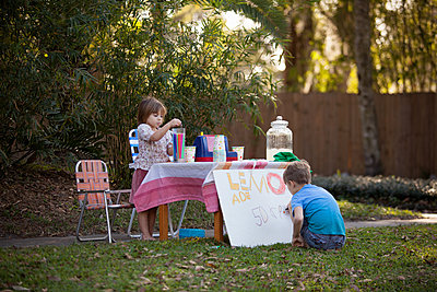 Boy and sister preparing lemonade stand sign in garden - p924m1447051 by Kinzie Riehm