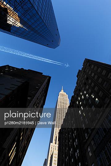 Passagierflugzeug am blauen Himmel über dem Empire State Building - p1280m2181945 von Dave Wall