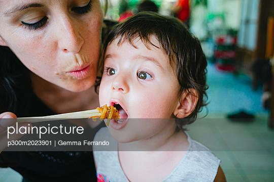 Thailand, Chiang Mai, Mother feeding her daughter with Pad Thai, using chopsticks - p300m2023901 von Gemma Ferrando