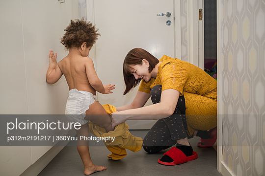 Mother helping daughter to get dressed - p312m2191217 by 360You Photography