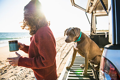 Woman and dog in the morning beach car camping - p1166m2285566 by Cavan Images