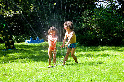 Children under the garden sprinkler - p1231m1041970 by Iris Loonen