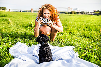 Germany, Cologne, portrait of smiling young woman on meadow taking picture of her dog - p300m2028988 by Jo Kirchherr