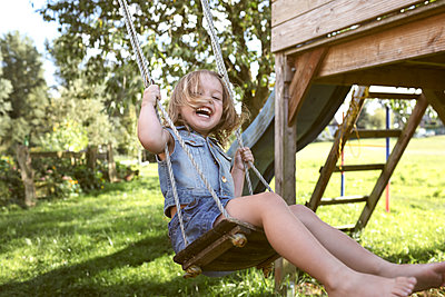Laughing little girl sitting on swing in the garden - p300m2070119 by Katharina Mikhrin