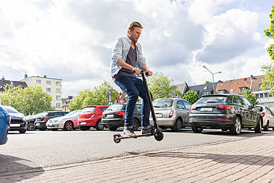Man on E-Scooter jumping in the air - p300m2114502 by Joseffson