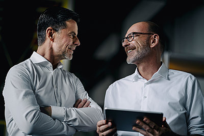 Two smiling men with tablet talking in a factory - p300m2171110 by Kniel Synnatzschke