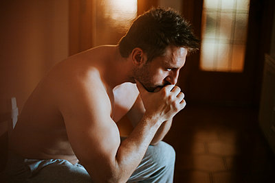 Close-up of shirtless thoughtful man sitting at home - p300m2206972 by Miguel Frias