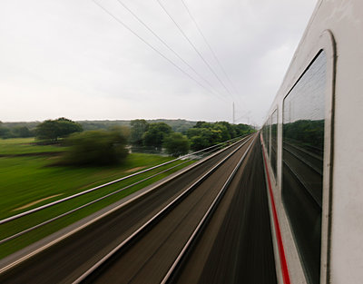 Germany; fast moving train in landscape - p300m919799 by Christian Richter