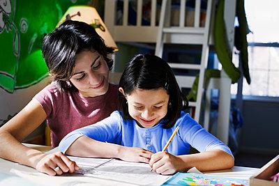 Hispanic mother helping daughter with homework - p555m1454140 by Jon Feingersh