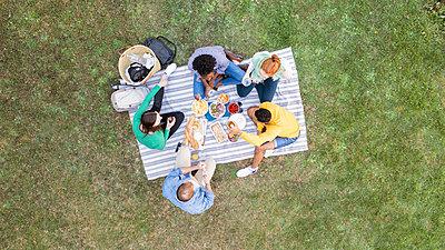 Happy young friends having a picnic in garden - p623m2294745 by Gabriel Sanchez