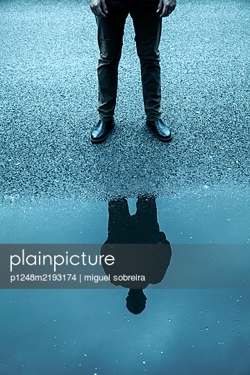 Man standing at puddle  - p1248m2193174 by miguel sobreira
