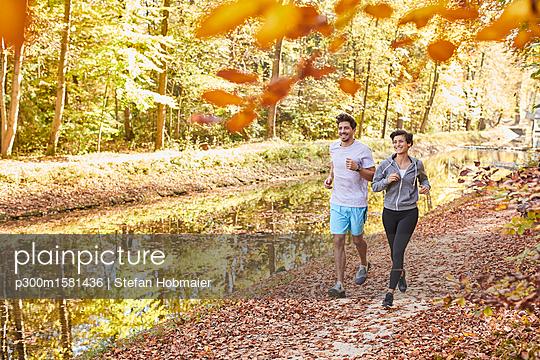 Couple jogging on autumnally forest track - p300m1581436 von Stefan Hobmaier