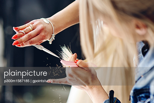 Close-up of hairdresser cutting woman's hair - p300m1587185 von gpointstudio