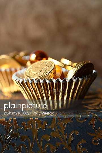 Chocolate coins in gold dish. - p349m2167802 by Polly Wreford